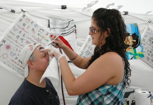 Rick Kingsbury, owner of TanFastics gets an air brush tattoo from Savannah