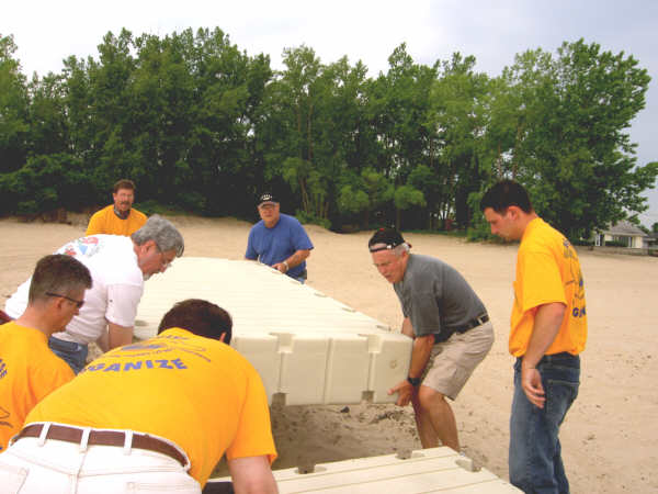 Volunteers including building trades union members and county officials work with Jim Beaudoin of Bluewater Docks, Algonac, right, to heft sections of a floating dock installed Friday at the Bay City State Recreation Area beach.